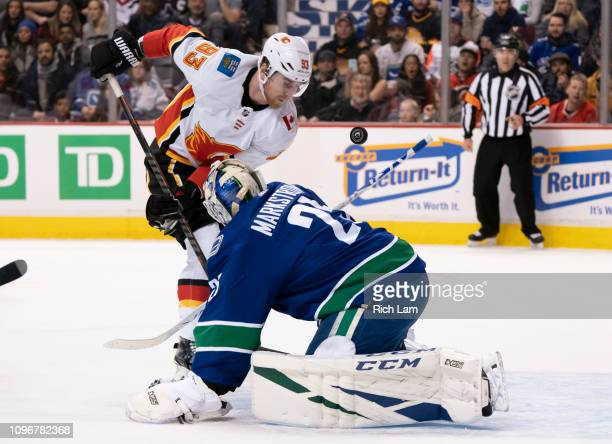 Sam Bennett of the Calgary Flames knocks the loose puck past goalie Jacob Markstrom of the Vancouver Canucks for a goal in NHL action on February...
