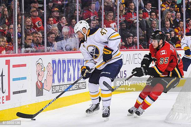 Sam Bennett of the Calgary Flames looks to check Zach Bogosian of the Buffalo Sabres during an NHL game at Scotiabank Saddledome on October 18 2016...