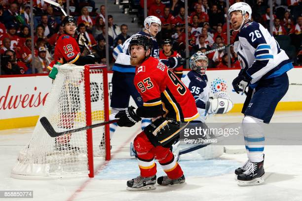 Sam Bennett of the Calgary Flames skates against Blake Wheeler of the Winnipeg Jets during an NHL game on October 7 2017 at the Scotiabank Saddledome...