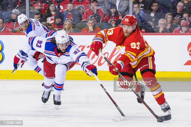 Sam Bennett of the Calgary Flames skates with the puck against Mika Zibanejad of the New York Rangers during an NHL game at Scotiabank Saddledome on...