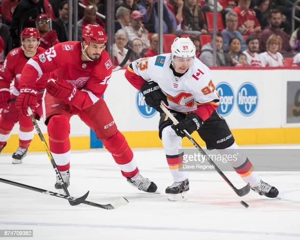Sam Bennett of the Calgary Flames skates with the puck in front of Jonathan Ericsson of the Detroit Red Wings during an NHL game at Little Caesars...