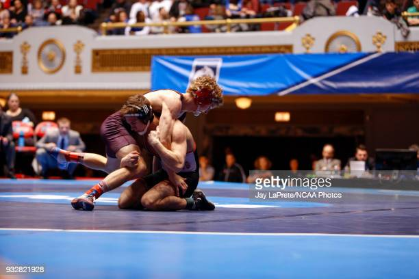 Sam Bennyhoff of Augsburg left wrestles Brock Rathbun of Wartburg in the 133 weight class during the Division III Men's Wrestling Championship held...