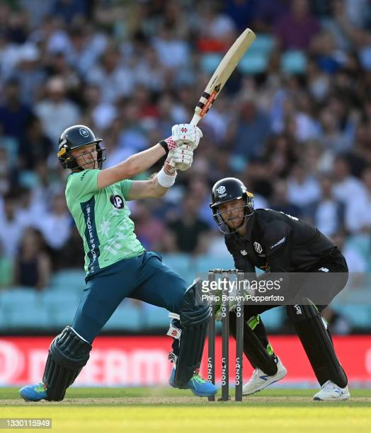Sam Billings of Oval Invincibles hits out watched by Jos Buttler of Manchester Originals during the Hundred match between Oval Invincibles and...