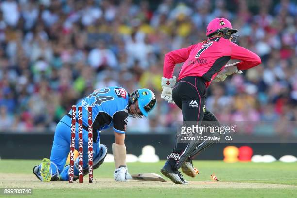 Sam Billings of the Sixers stumps Travis Head of the Strikers during the Big Bash League match between the Sydney Sixers and the Adelaide Strikers at...
