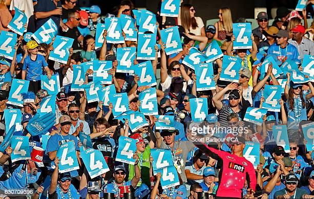 ADELAIDE AUSTRALIA DECEMBER Sam Billings of the Sixers throws the ball back as Strikers fans in the crowd hold up signs as a four is hit during the...