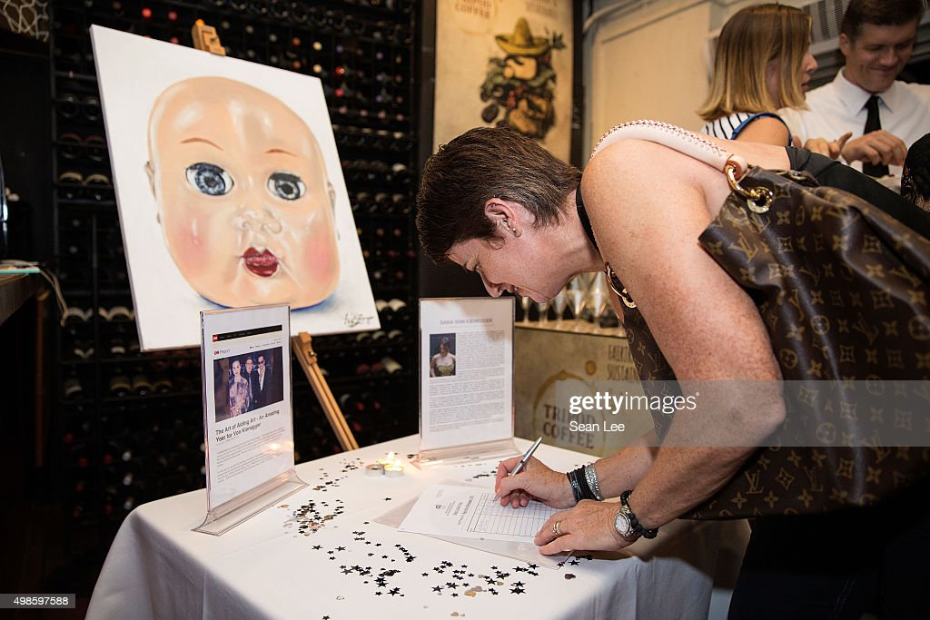 Sam Blakey bids for Sara Von Kieneggers painting at the Original Sin hosted charity fund raising party for the benefit of Truyen Tin Orphanage on November 21, 2015 in Singapore.