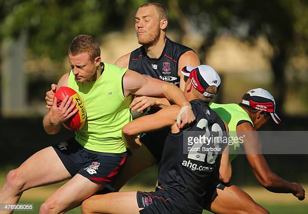Sam Blease is tackled by Bernie Vince and Dean Terlich during a Melbourne Demons AFL training session at Gosch's Paddock on March 6 2014 in Melbourne...