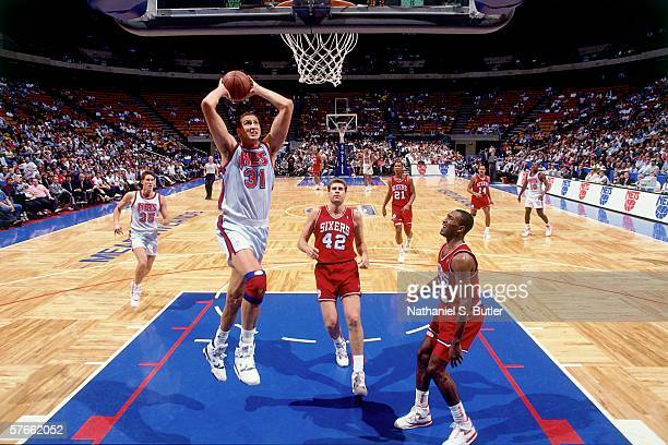 Sam Bowie of the New Jersey Nets takes the ball to the basket for a dunk against Mike Gminski of the Philadelphia 76ers during a game circa 1991 at...