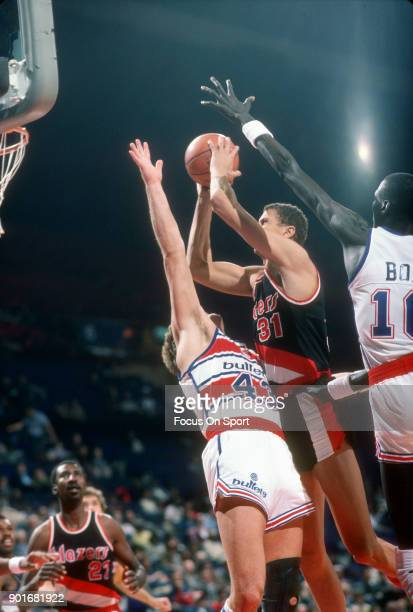 Sam Bowie of the Portland Trail Blazers goes up to shoot over Jeff Ruland of the Washington Bullets during an NBA basketball game circa 1986 at the...