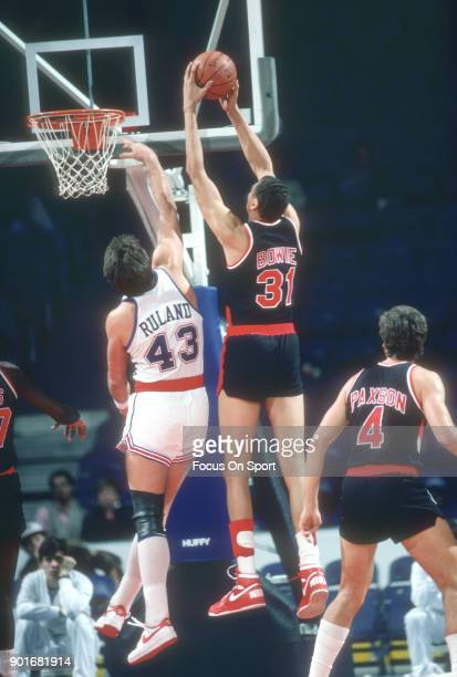 Sam Bowie of the Portland Trail Blazers grabs a rebound over Jeff Ruland of the Washington Bullets during an NBA basketball game circa 1986 at the...