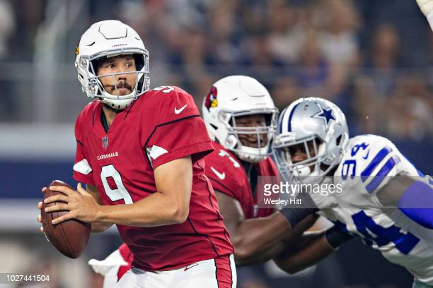 Sam Bradford of the Arizona Cardinals drops back to pass and is sacked by Randy Gregory of the Dallas Cowboys at ATT Stadium during week 3 of the...