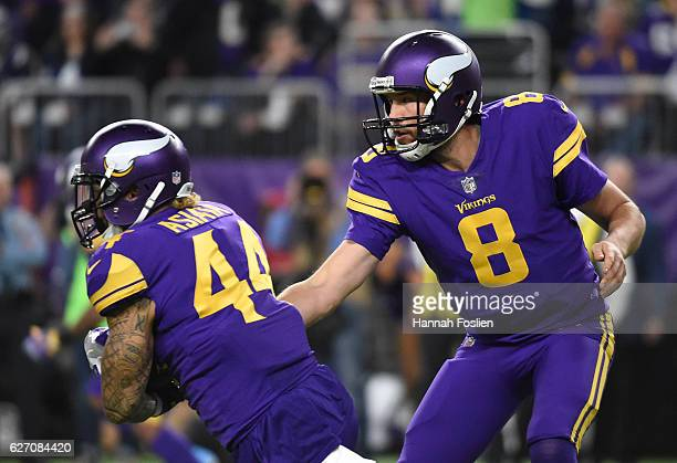 Sam Bradford of the Minnesota Vikings hands the ball off to Matt Asiata in the first half of the game against the Dallas Cowboys on December 1 2016...