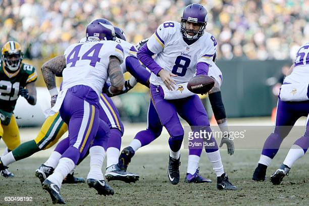 Sam Bradford of the Minnesota Vikings hands the ball off to Matt Asiata in the first quarter against the Green Bay Packers at Lambeau Field on...