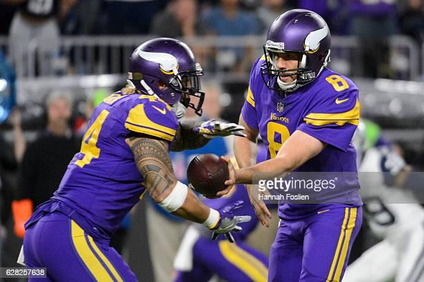 Sam Bradford of the Minnesota Vikings hands the ball to teammate Matt Asiata during the game on December 1 2016 at US Bank Stadium in Minneapolis...