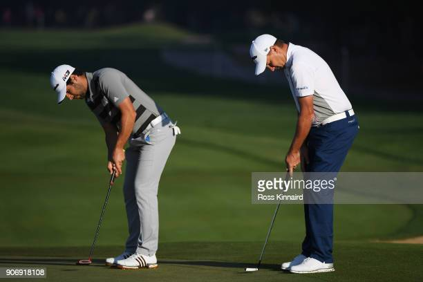 Sam Brazel of Australia and Alvaro Quiros of Spain line up their putts on the second green during round two of the Abu Dhabi HSBC Golf Championship...