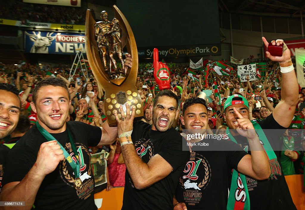 Sam Burgess, Greg Inglis and Dylan Walker of the Rabbitohs pose with the trophy in front of the crowd after victory during the 2014 NRL Grand Final match between the South Sydney Rabbitohs and the Canterbury Bulldogs at ANZ Stadium on October 5, 2014 in Sydney, Australia.