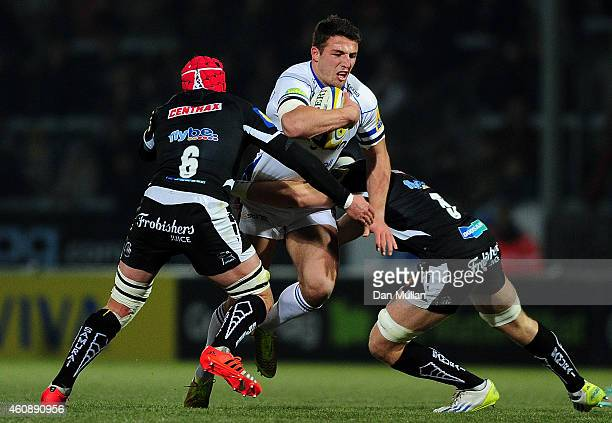 Sam Burgess of Bath is tackled by Tom Johnson and Ed Holmes of Exeter Braves during the Aviva Premiership A League match between Exeter Braves and...