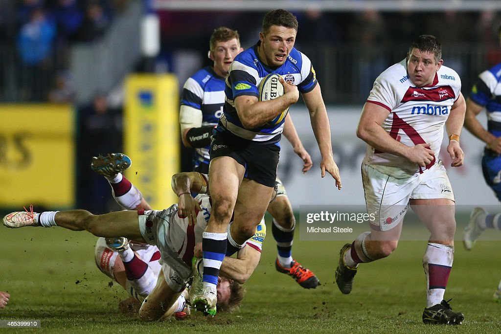 Sam Burgess of Bath powers through a challenge as Eifion Lewis Roberts (R) of Sale looks on during the Aviva Premiership match between Bath Rugby and Sale at the Recreation Ground on March 6, 2015 in Bath, England.