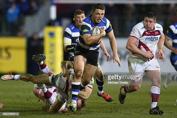 Sam Burgess of Bath powers through a challenge as Eifion Lewis Roberts of Sale looks on during the Aviva Premiership match between Bath Rugby and...