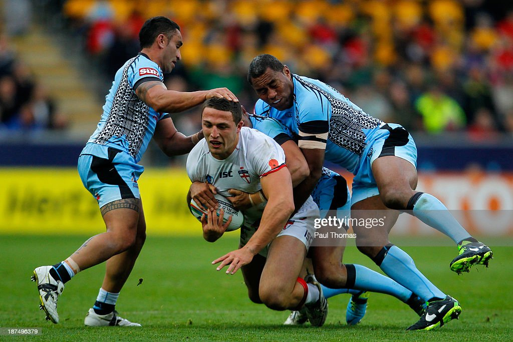 Sam Burgess (C) of England is tackled by James Storer (L), Daryl Millard and Petero Civoniceva (R) of Fiji during the Rugby League World Cup Group A match at the KC Stadium on November 9, 2013 in Hull, England.