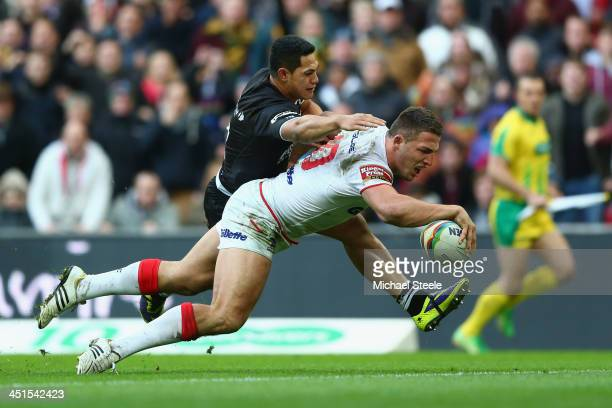 Sam Burgess of England scores his sides third try despite the attention from Roger TuivasaScheck of New Zealand during the Rugby League World Cup...