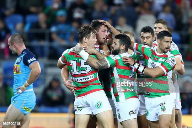 Sam Burgess of the Rabbitohs celebrates a try with team mates during the round 14 NRL match between the Gold Coast Titans and the South Sydney...