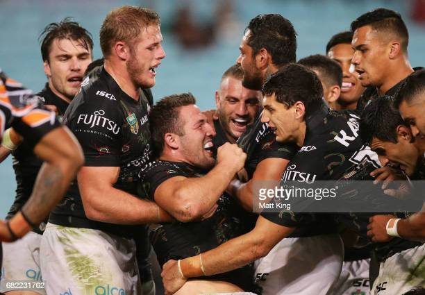 Sam Burgess of the Rabbitohs celebrates with team mates after scoring his second try during the round ten NRL match between the Wests Tigers and the...