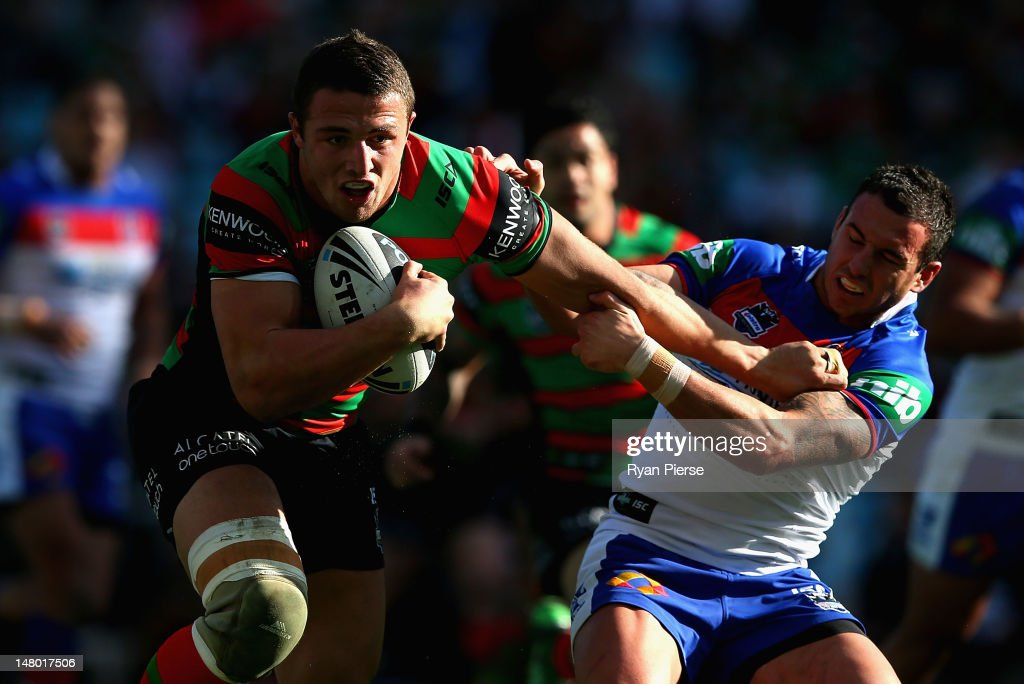 Sam Burgess of the Rabbitohs is tackled by Danny Buderus of the Knights during the round 18 NRL match between the South Sydney Rabbitohs and the Newcastle Knights at ANZ Stadium on July 8, 2012 in Sydney, Australia.
