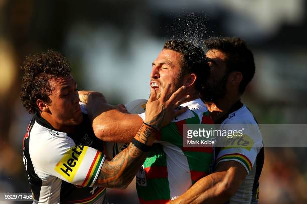 Sam Burgess of the Rabbitohs is tackled by James FisherHarris and James Tamou of the Panthers during the round two NRL match between the Penrith...