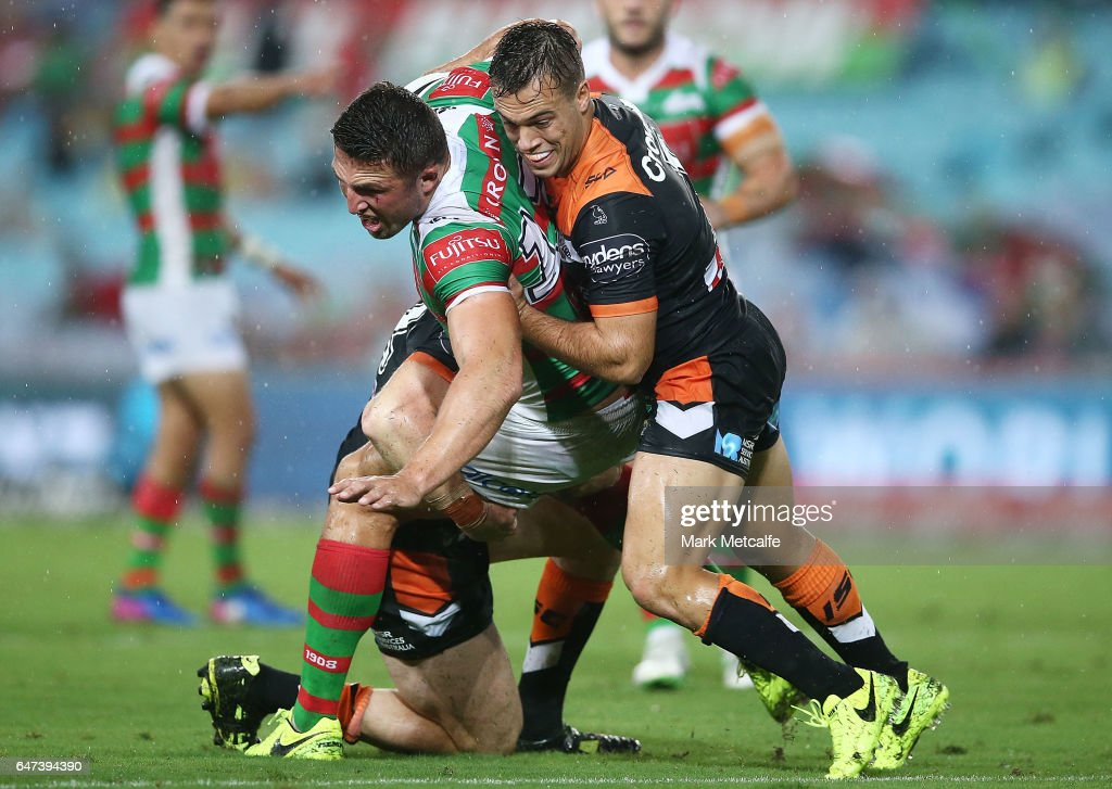 Sam Burgess of the Rabbitohs is tackled by Luke Brooks of the Tigers during the round one NRL match between the South Sydney Rabbitohs and the Wests Tigers at ANZ Stadium on March 3, 2017 in Sydney, Australia.