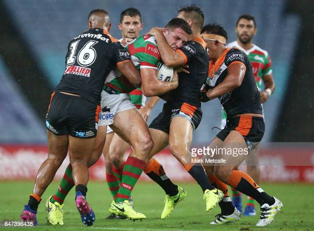 Sam Burgess of the Rabbitohs is tackled by Luke Brooks of the Tigers during the round one NRL match between the South Sydney Rabbitohs and the Wests...