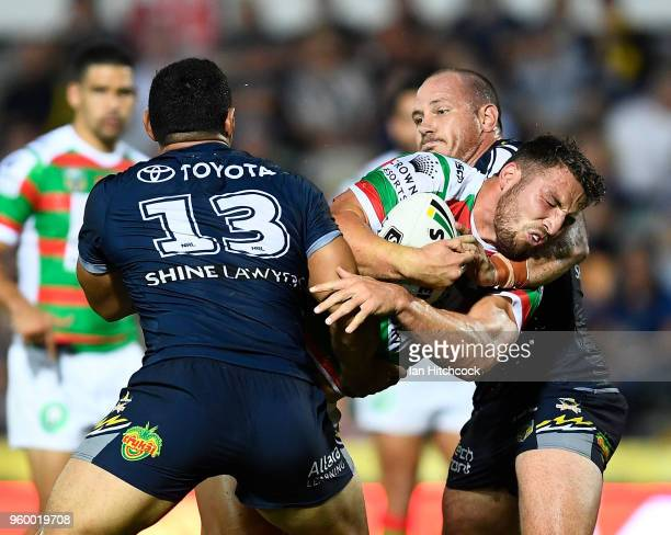 Sam Burgess of the Rabbitohs is tackled by Matthew Scott and Jason Taumalolo of the Cowboys during the round 11 NRL match between the North...