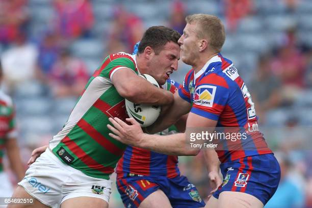 Sam Burgess of the Rabbitohs is tackled by Mitchell Barnett of the Knights during the round three NRL match between the Newcastle Knights and the...