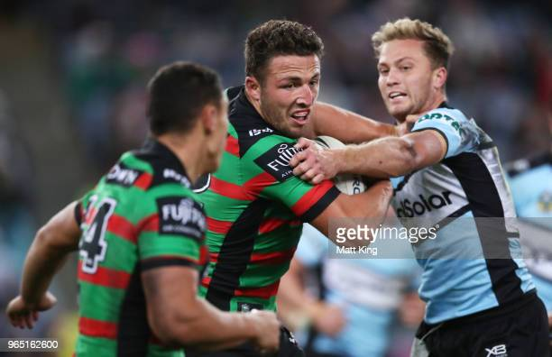 Sam Burgess of the Rabbitohs is tackled during the round 13 NRL match between the South Sydney Rabbitohs and the Cronulla Sharks at ANZ Stadium on...