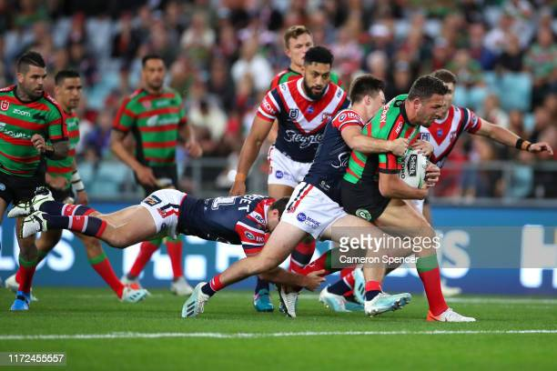 Sam Burgess of the Rabbitohs is tackled during the round 25 NRL match between the South Sydney Rabbitohs and the Sydney Roosters at ANZ Stadium on...