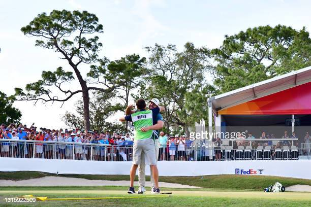 Sam Burns of the United States celebrates with his caddie on the 18th green after winning during the final round of the Valspar Championship on the...