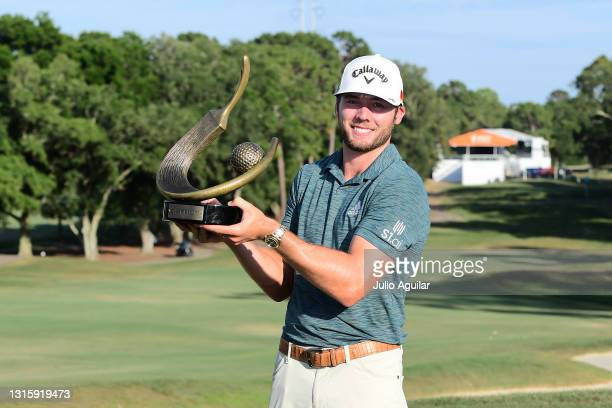 Sam Burns of the United States celebrates with the trophy after winning during the final round of the Valspar Championship on the Copperhead Course...