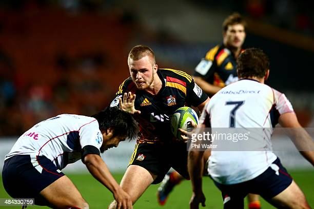 Sam Cane of the Chiefs fends off Shota Horie of the Rebels during the round nine Super Rugby match between the Chiefs and the Rebels at Waikato...
