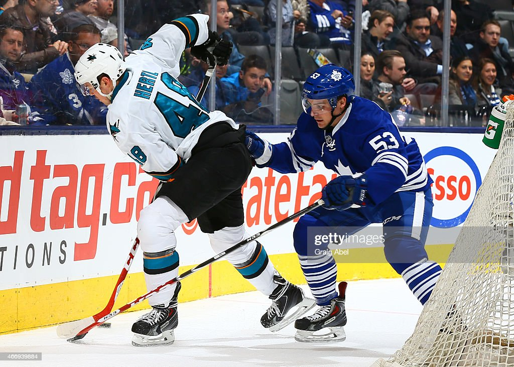 Sam Carrick #53 of the Toronto Maple Leafs battles with Tomas Hertl #48 of the San Jose Sharks during game action on March 19, 2015 at Air Canada Centre in Toronto, Ontario, Canada.
