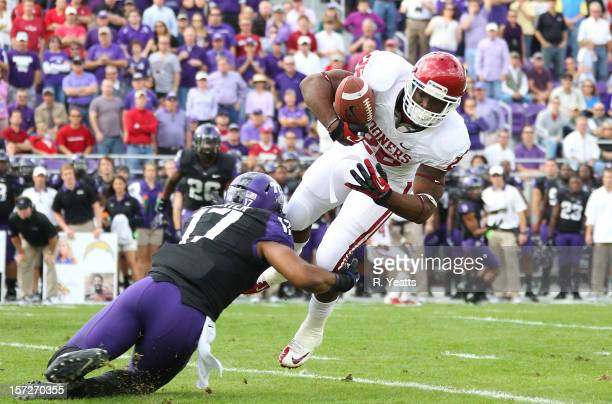 Sam Carter of the TCU Horned Frogs tackles Damien Williams of the Oklahoma Sooners at Amon G Carter Stadium on December 1 2012 in Fort Worth Texas