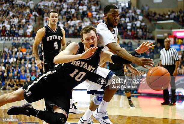 Sam Cassell Jr #10 of the Connecticut Huskies reaches for a loose ball in front of Joe O'Shea of the Bryant Bulldogs in the first half during the...