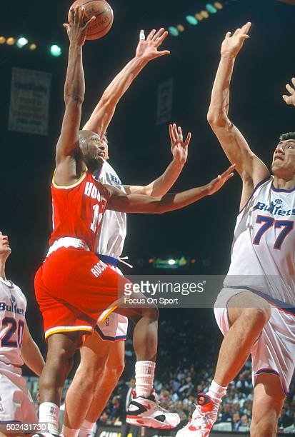 Sam Cassell of the Houston Rockets shoots over Gheorghe Muresan of the Washington Bullets during an NBA basketball game circa 1994 at the US Airway...