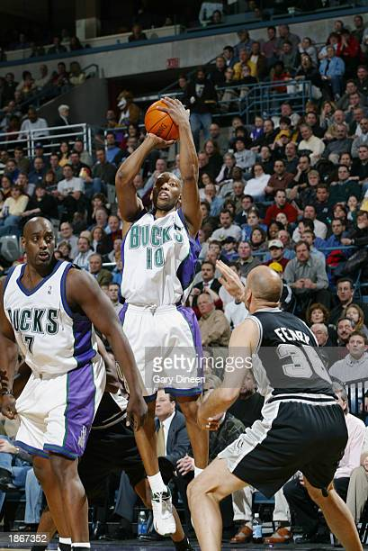 Sam Cassell of the Milwaukee Bucks shoots over Danny Ferry of the San Antonio Spurs during the game at Bradley Center on March 11 2003 in Milwaukee...