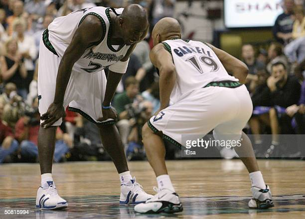 Sam Cassell of the Minnesota Timberwolves crouches down to talk to Kevin Garnett in the second half against the Sacramento Kings in Game 2 of the NBA...
