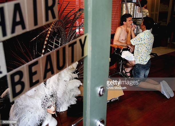 Sam Chalotorn applies makeup for partner Brad Merriel prior to the start of the 2006 Sydney New Gay and Lesbian Mardi Gras parade March 4 2006 in...