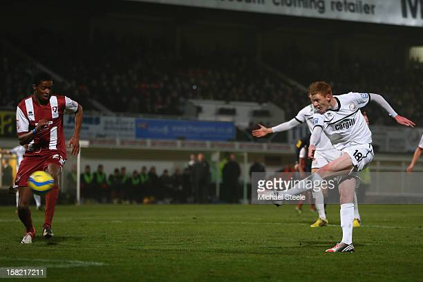 Sam Clucas of Hereford United shoots as Sido Jombati of Cheltenham Town looks on during the FA Cup with Budweiser Second Round Replay match between...