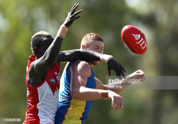 Sam Collins of the Suns is challenged by Aliir Aliir of the Swans during the 2019 JLT Community Series AFL match between the Sydney Swans and the...