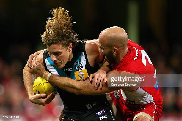 Sam Colquhoun of the Power is tackled by Jarrad McVeigh of the Swans during the round 14 AFL match between the Sydney Swans and the Port Adelaide...