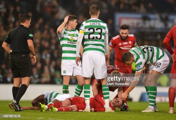 Sam Cosgrove of Aberdeen assists injured team mate Gary MackaySteven of Aberdeen as he clashes heads with Dedryck Boyata of Celtic during the Betfred...
