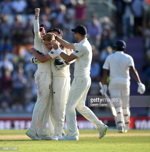 Sam Curran of England celebrates with captain Joe Root and James Anderson after dismissing Ravichandran Ashwin of India to win the Specsavers 4th...